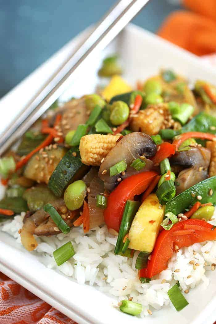 Closeup of Stir Fry Veggies over rice on a white plate