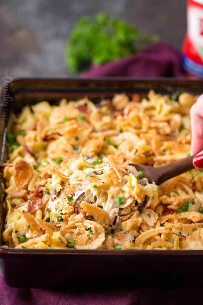 Cheesy chicken noodle casserole in a serving dish being scooped with a wooden spoon.