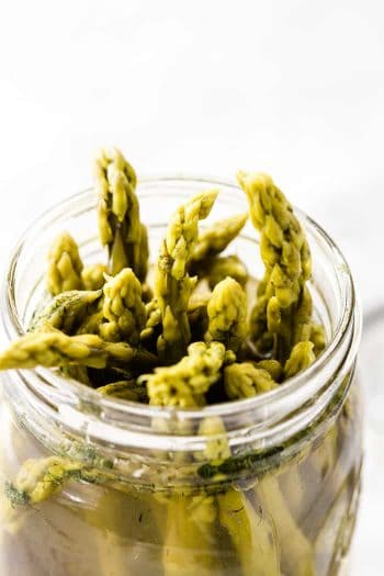 The tops of pickled asparagus peeking out of a canning jar