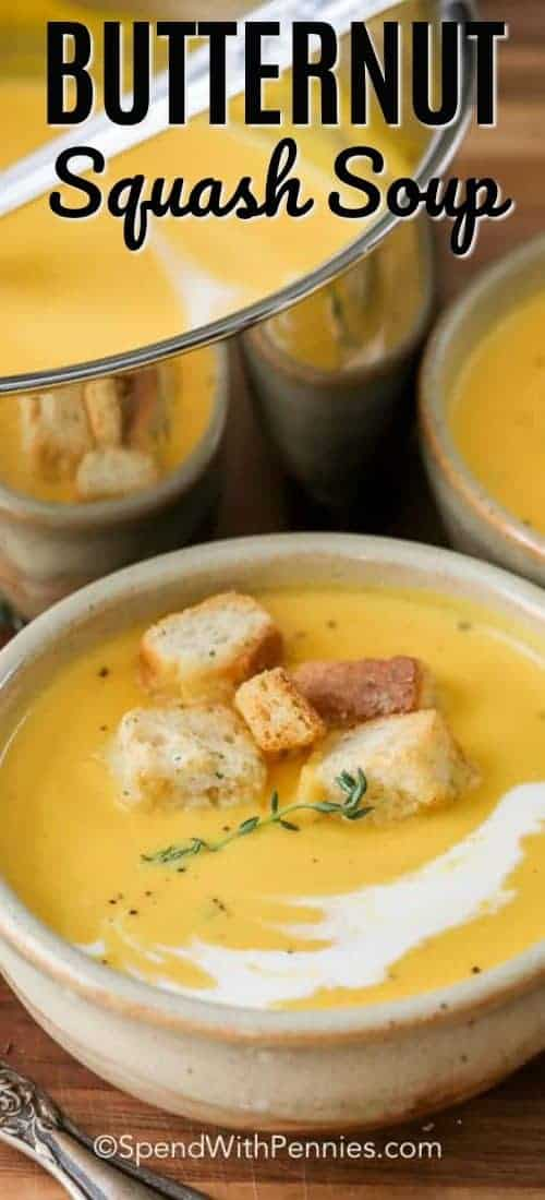 Butternut squash soup in a bowl garnished with croutons and a sprig of thyme