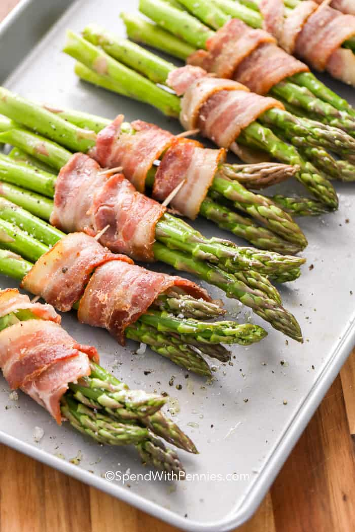 Asparagus wrapped in bacon secured with toothpicks on a baking sheet.