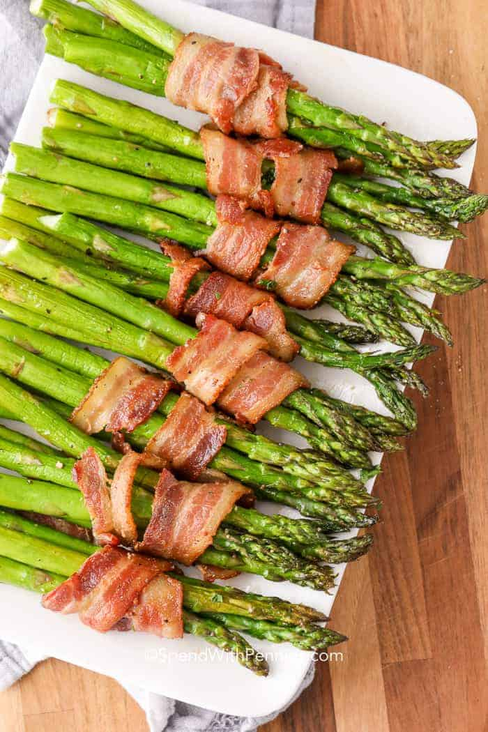 Bacon wrapped asparagus on a white serving dish.