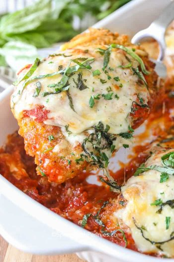 Classic Chicken Parmesan topped with fresh basil being served out of a baking dish