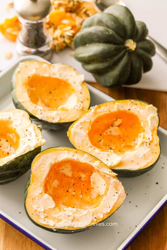 Acorn squash in a baking dish ready to bake topped with butter, brown sugar, salt and pepper.