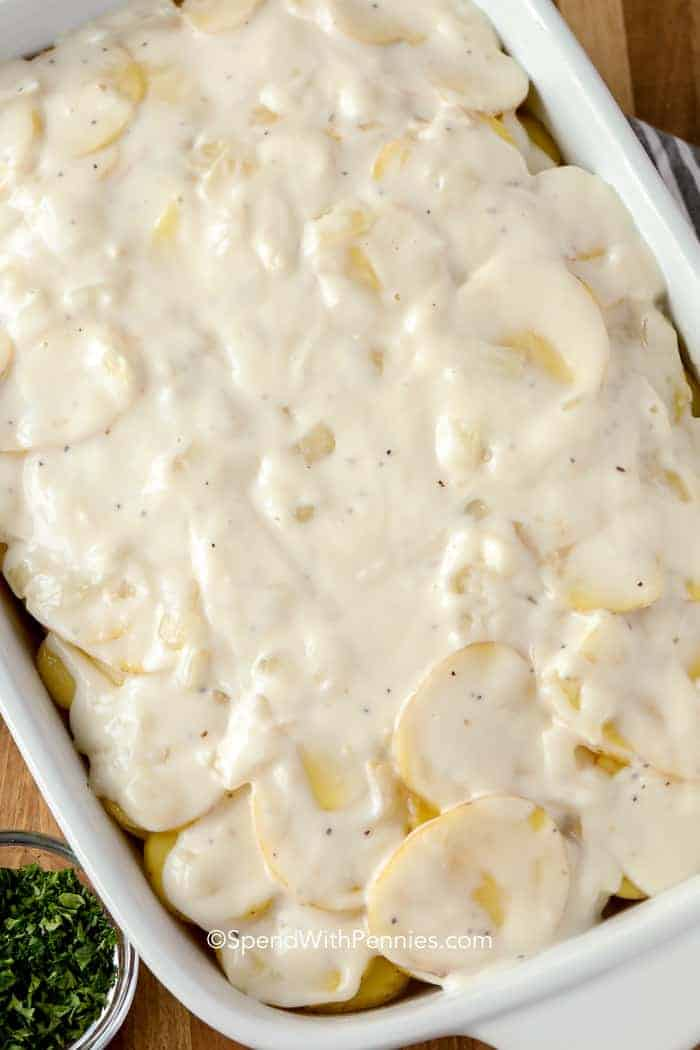 A pan of raw scalloped potatoes with parsley on the side