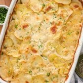 A pan of baked scalloped potatoes with parsley on the side