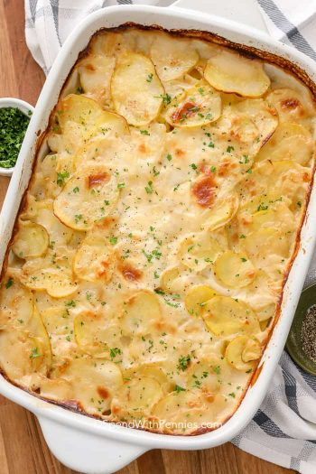 baked scalloped potatoes in dish with herbs