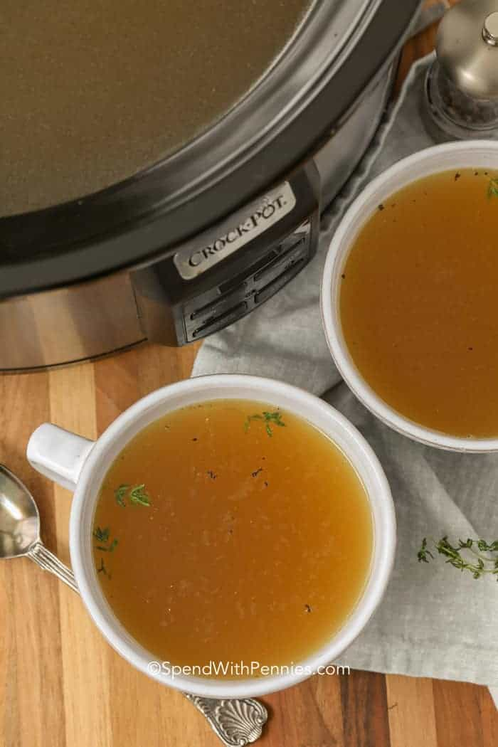 Rich turkey stock in white bowls next to a Crock Pot.