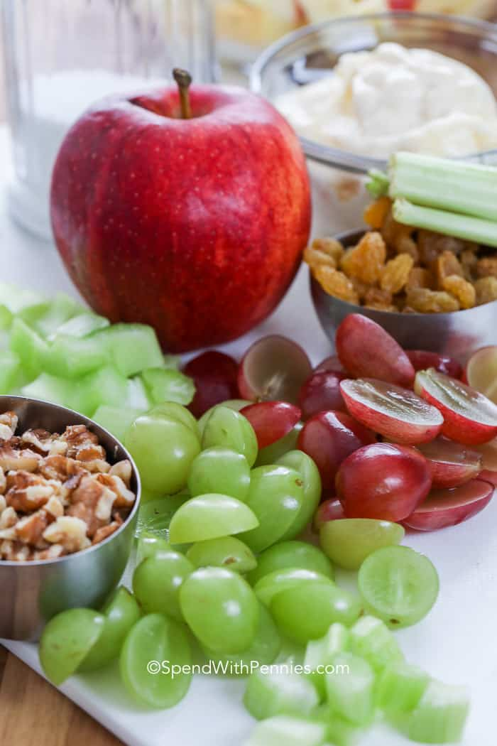 Waldorf salad ingredients: grapes, celery, apples, and walnuts on a cutting board.
