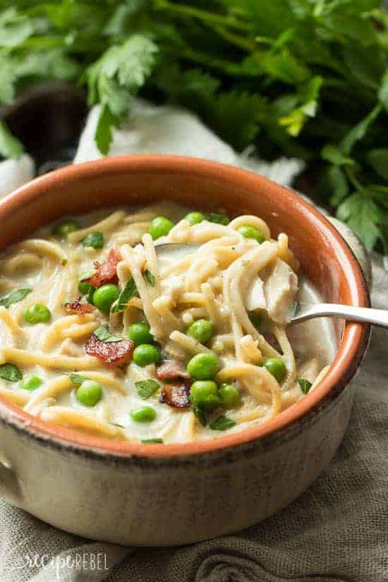 Turkey tetrazzini soup using leftover turkey in a bowl filled with noodles, peas, and cheese.
