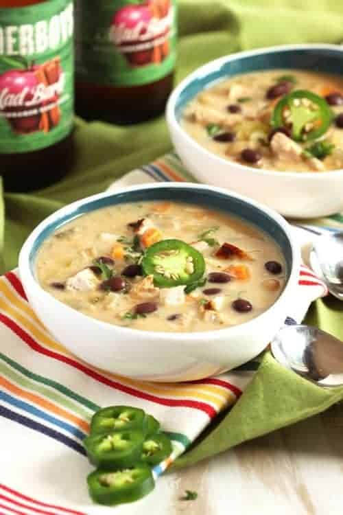 Leftover turkey tortilla soup in a white and blue bowl topped with a fresh jalapeno.