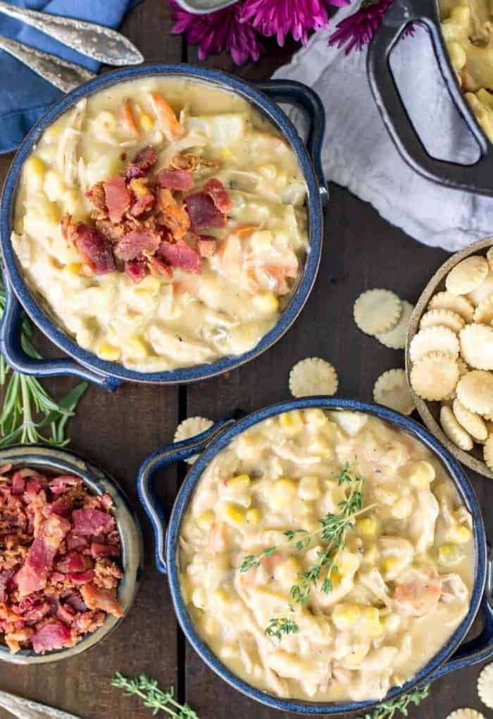 Bowls of turkey chowder packed full of corn, carrots, and topped with bacon.