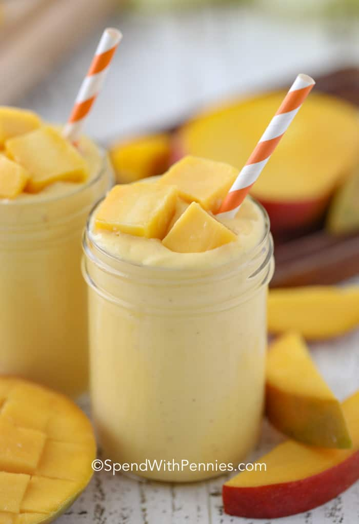 Mango Smoothie Recipe in cups with chunks of fresh mango