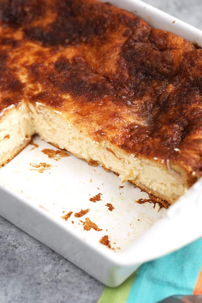 Sopapilla Cheesecake in a white dish with squares cut from it