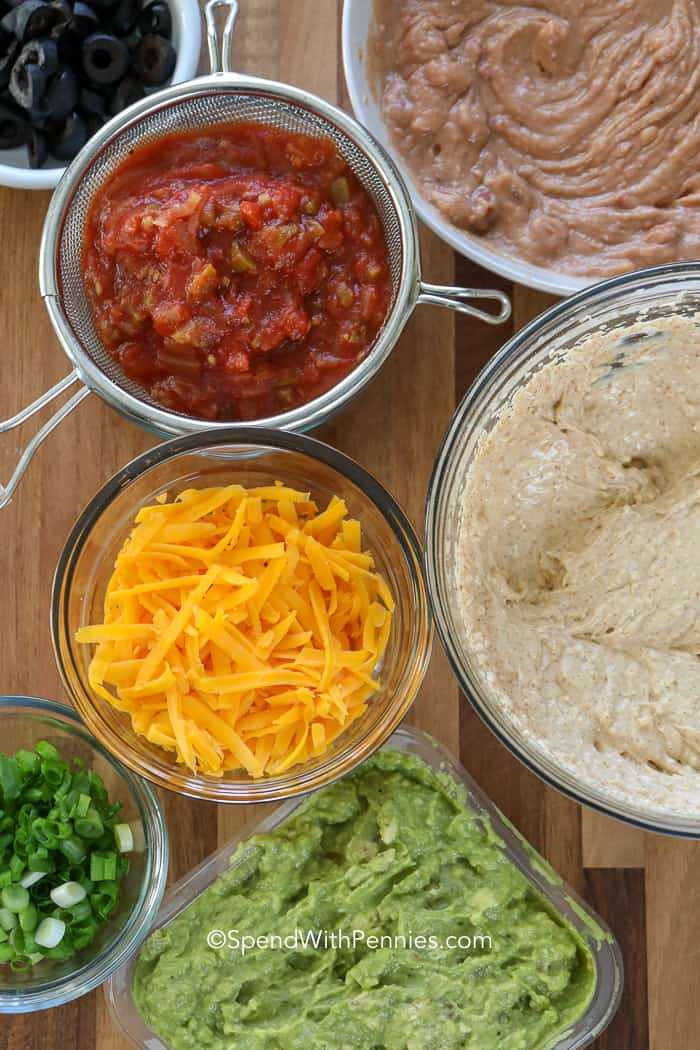 Ingredients for 7 layer dip like salsa, cheddar cheese, refried beans, and guacamole.