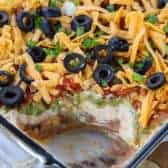 7 Layer Dip in a casserole dish with a scoop taken out