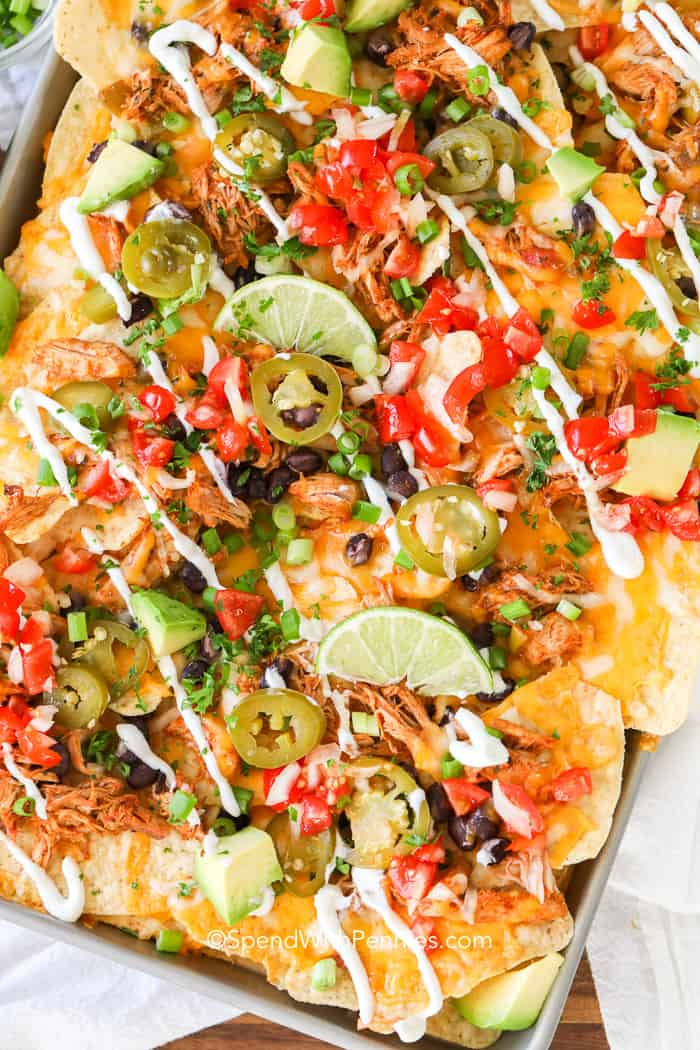 Sheet pan with Loaded Nachos with lime wedges