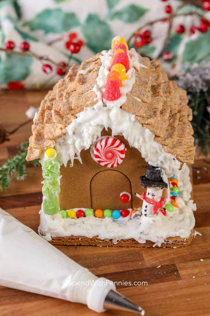 Gingerbread house icing next to a decorated gingerbread house