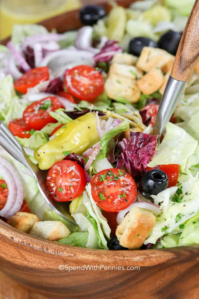 Italian salad in a wooden bowl being served.