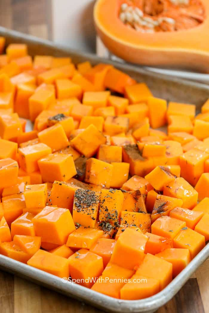 Peeled and cubed Roasted Butternut Squash on a baking sheet sprinkled with herbs, waiting to be roasted
