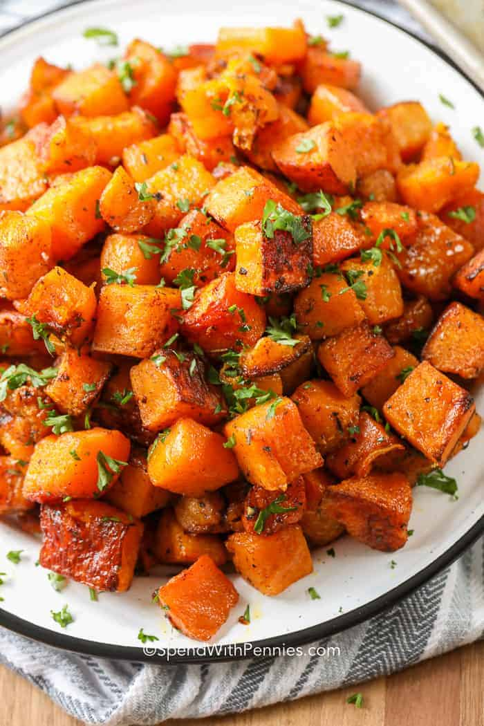 Perfectly browned Roasted Butternut Squash piled on a plate and garnished with parsley