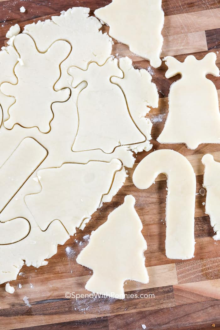 Sugar cookie dough being cut into Christmas shapes on a wooden cutting board.