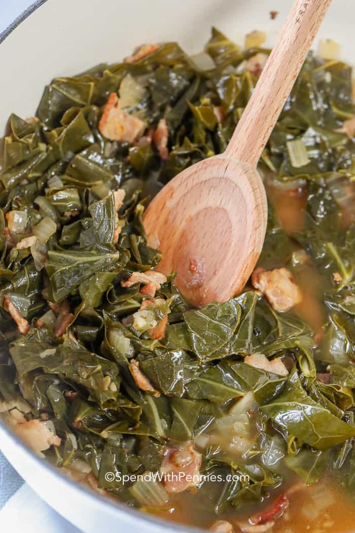 Cooked collard greens in a dutch oven with a wooden spoon.