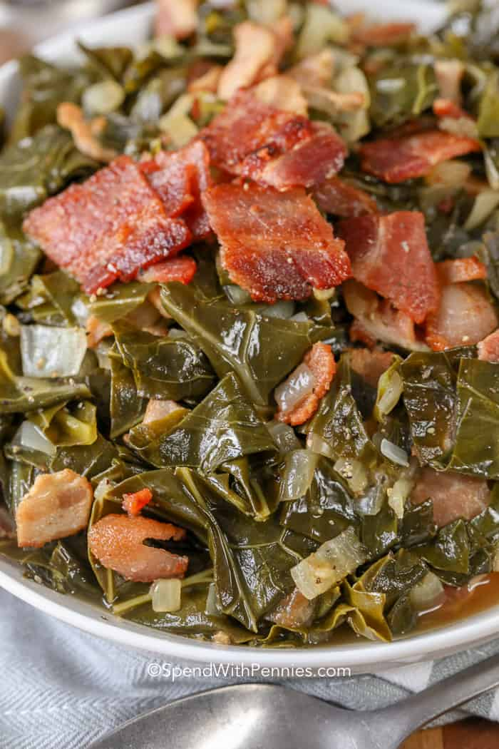 A bowl of collard greens topped with crispy bacon and onions.