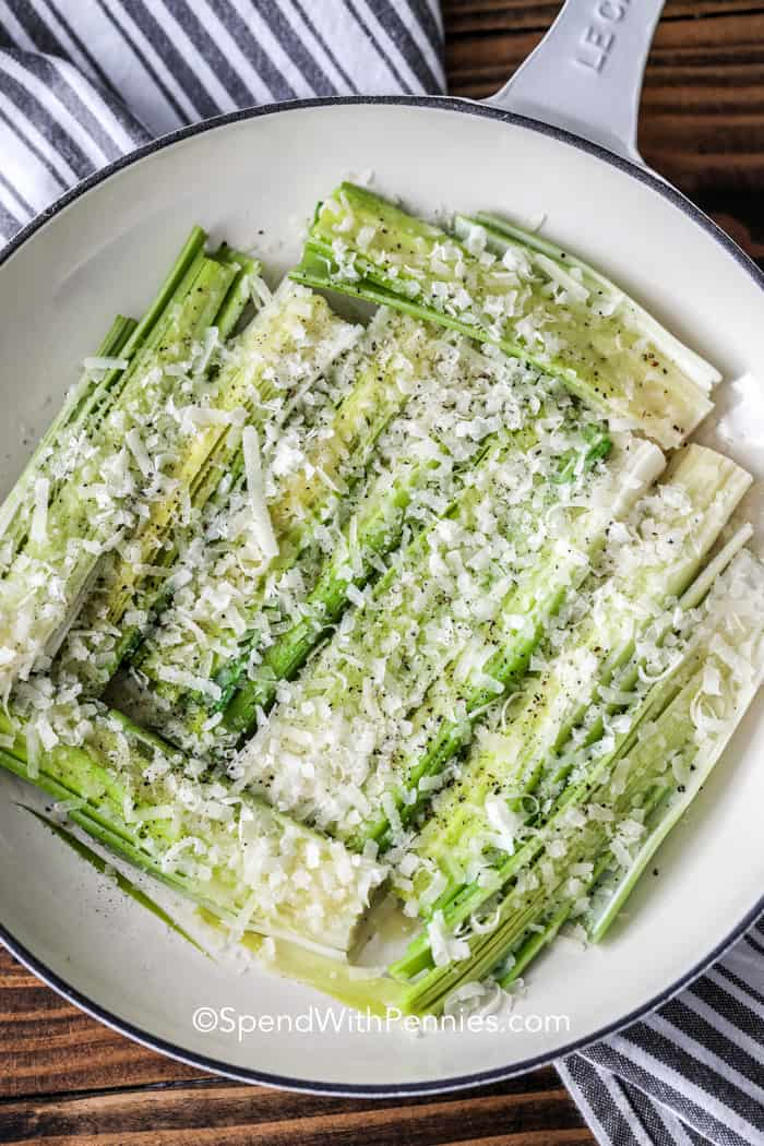 Steamed leeks covered in olive oil and parmesan cheese ready to be roasted.