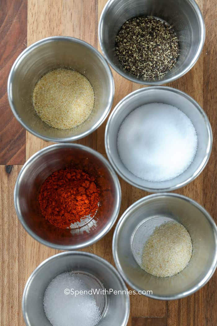 Homemade seasoned salt ingredients in individual silver bowls.