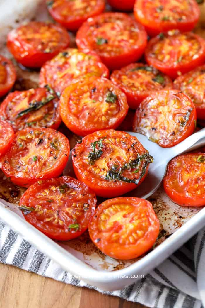 Roasted tomatoes being served with a silver spoon.