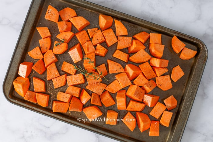 Roasted sweet potatoes peeled and cut on a pan, ready to be baked