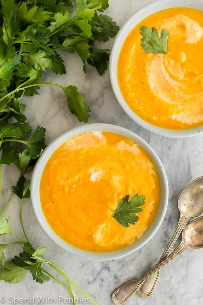 overhead of carrot soup recipe in two bowls, garnished with parsley, with two spoons on the side