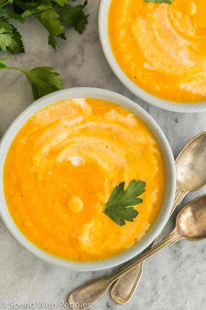 bowls of carrot soup, garnished with parsley, close up overhead with spoons on the side