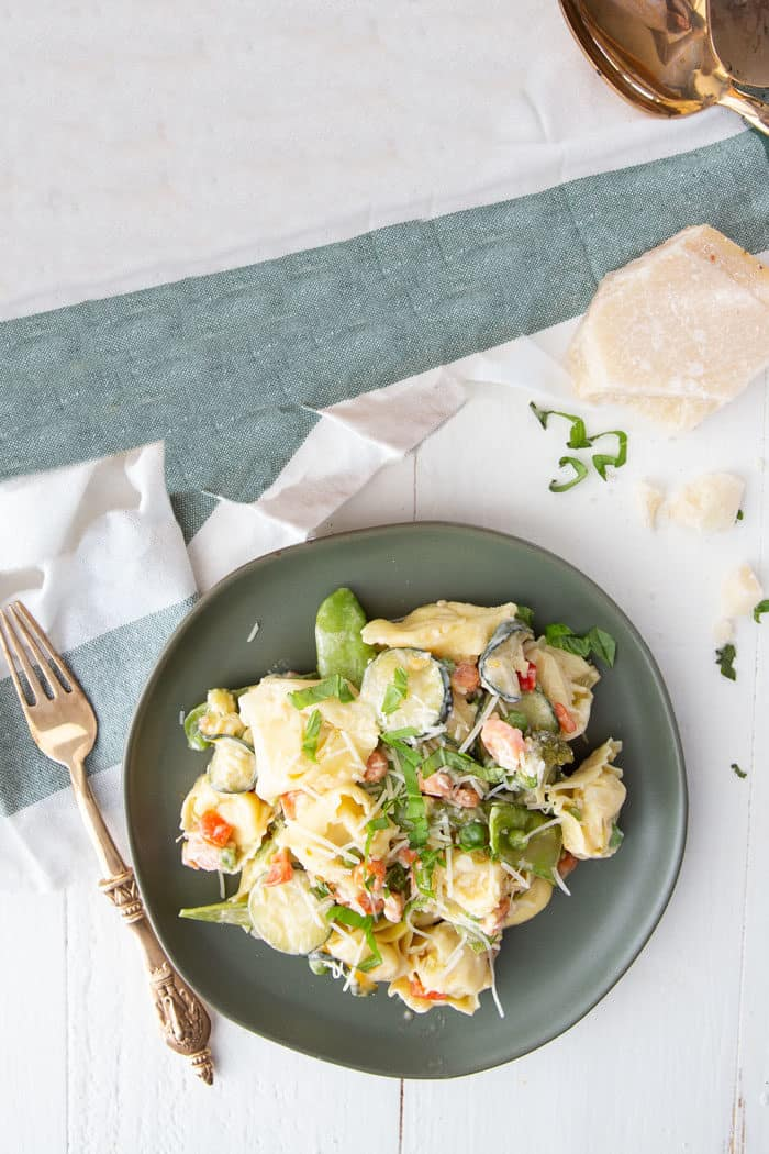 Pasta primavera with a white and green napkin and parmesan chunks