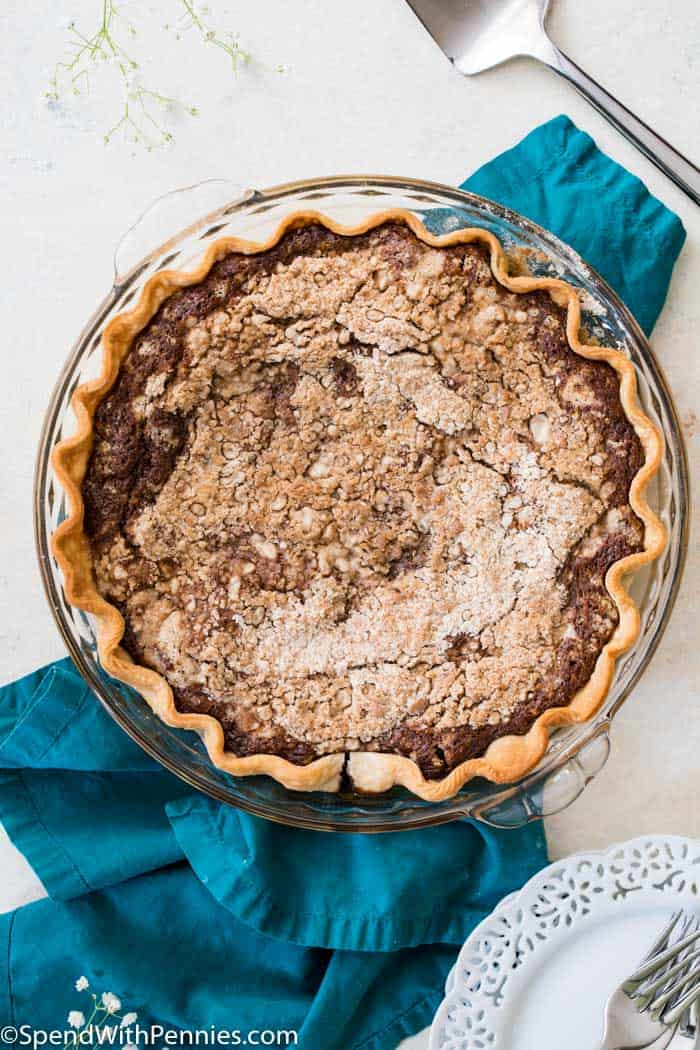 Overhead view of entire shoofly pie on a blue cloth with serving utensil and white plates in the background