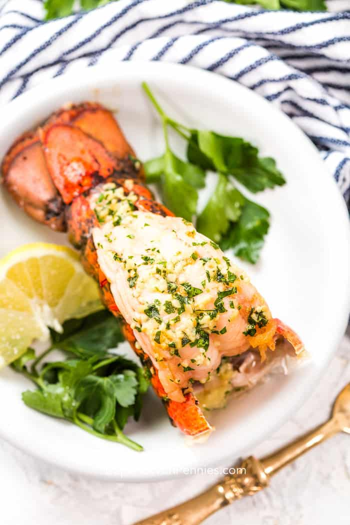 Broiled lobster tail on a white plate with fresh parsley, lemon slice, and a blue and white napkin and gold fork in the background