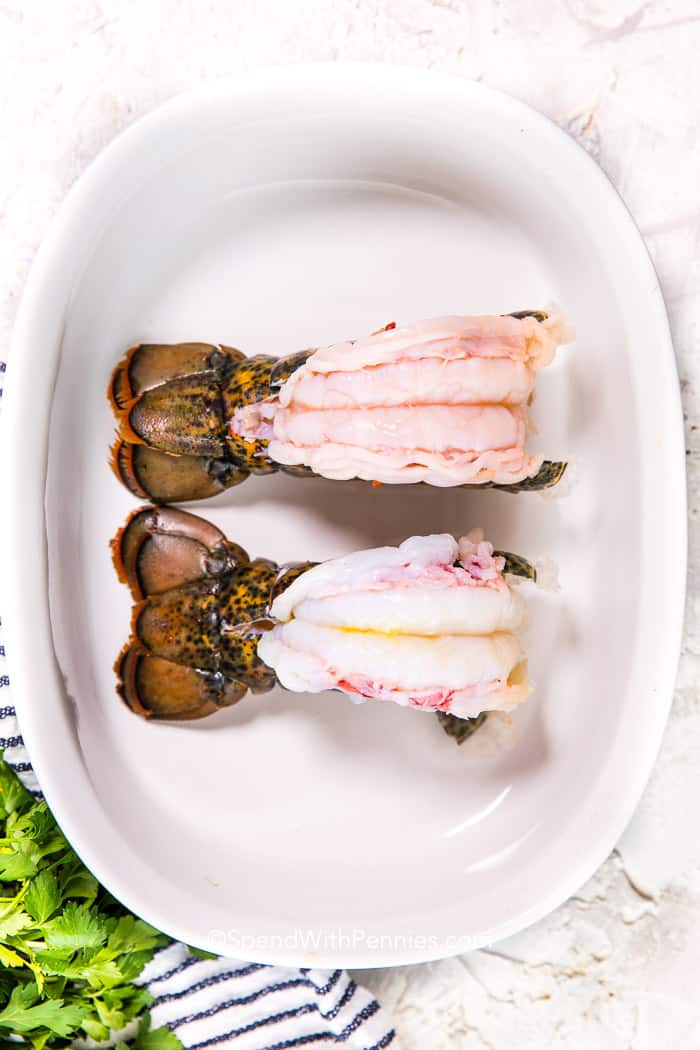 Two butterflied lobster tails in a white baking dish ready for the oven