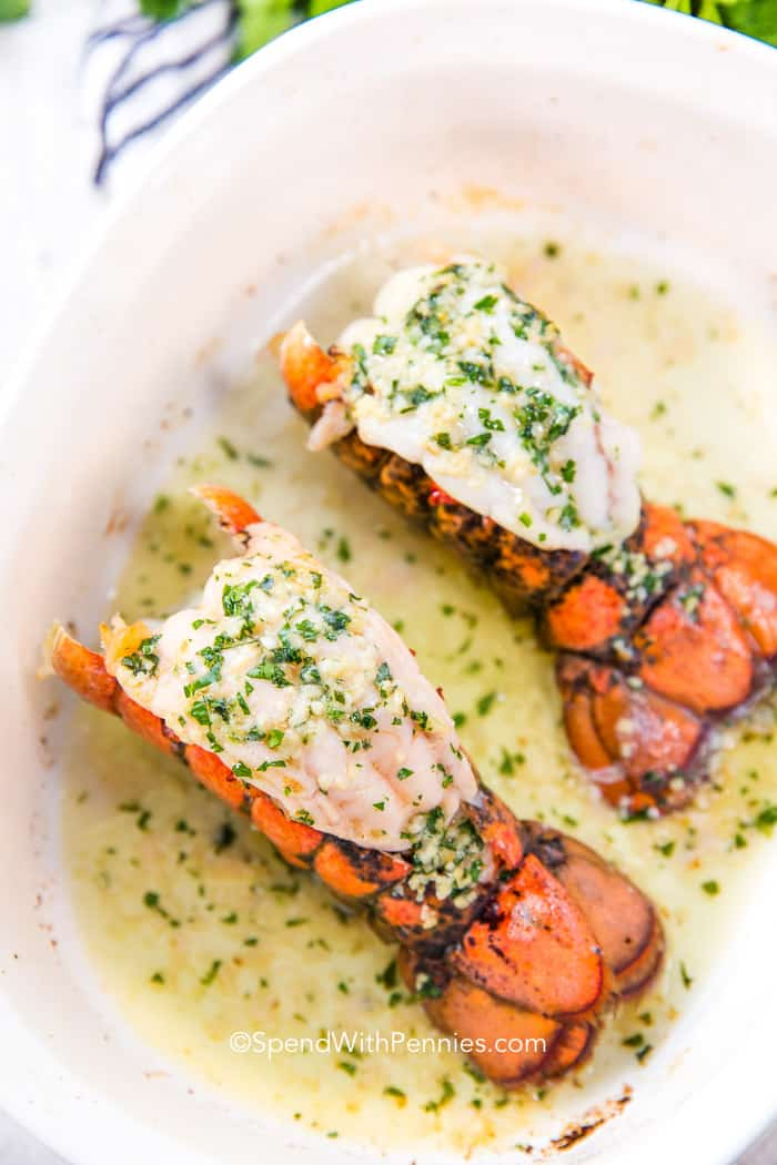 Two cooked lobster tails with butter sauce with garlic and parsley in a white baking dish