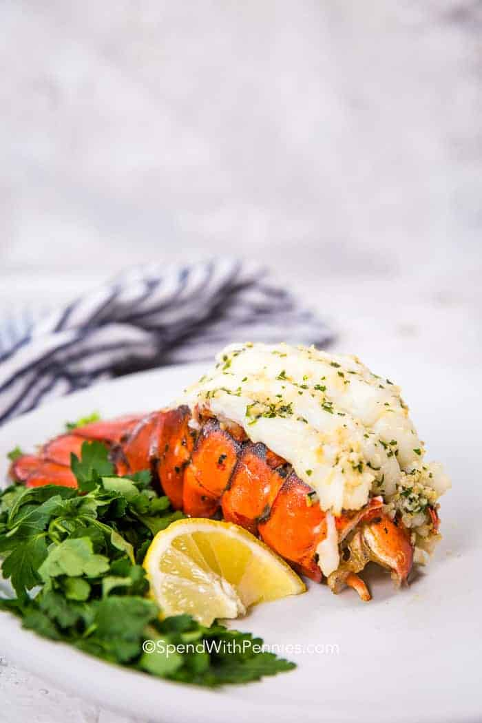 Broiled lobster tail with a lemon wedge and fresh parsley on a white plate and a napkin in the background