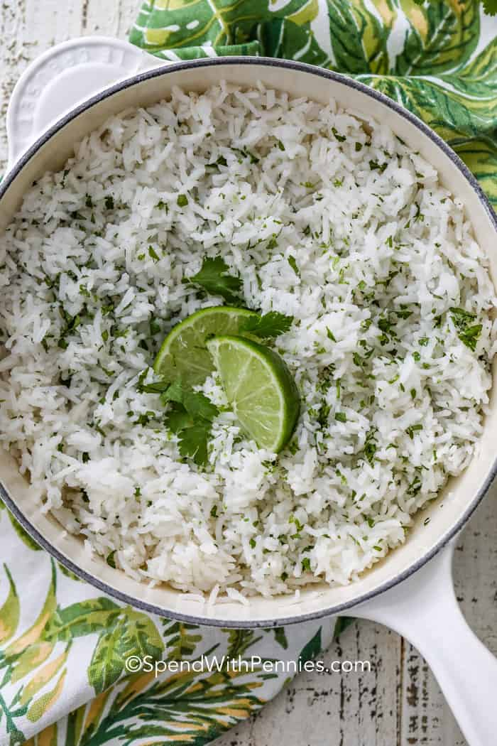 A pot of cilantro lime rice ready to serve topped with lime wedges and cilantro.