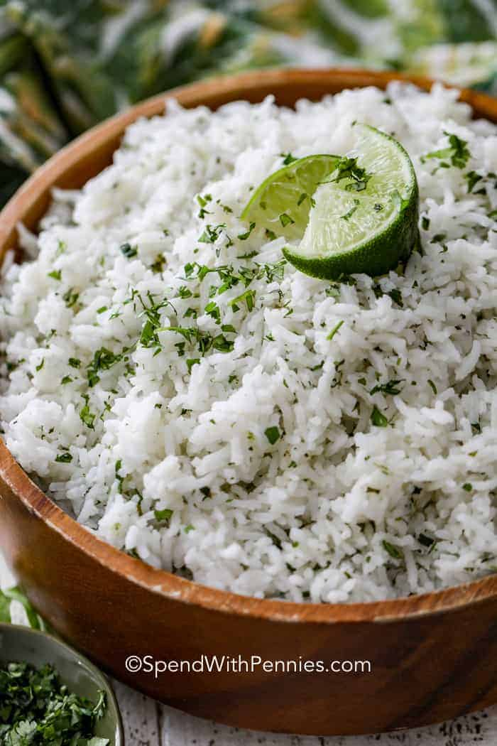 A wooden bowl of cilantro lime rice topped with chopped cilantro and lime wedges.
