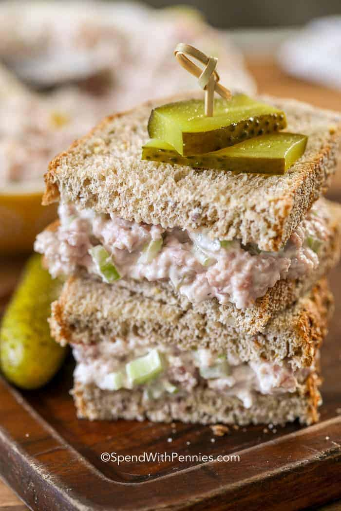 A ham salad sandwich cut in half with a pickle on top of it.