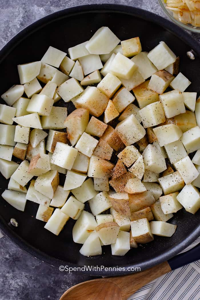 Uncooked potatoes in a pan with seasonings
