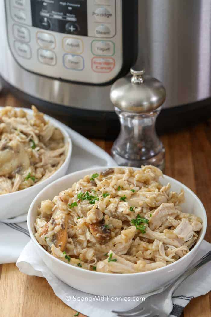 A bowl of Instant Pot chicken and rice with a pepper shaker next to it and an Instant Pot in the background.