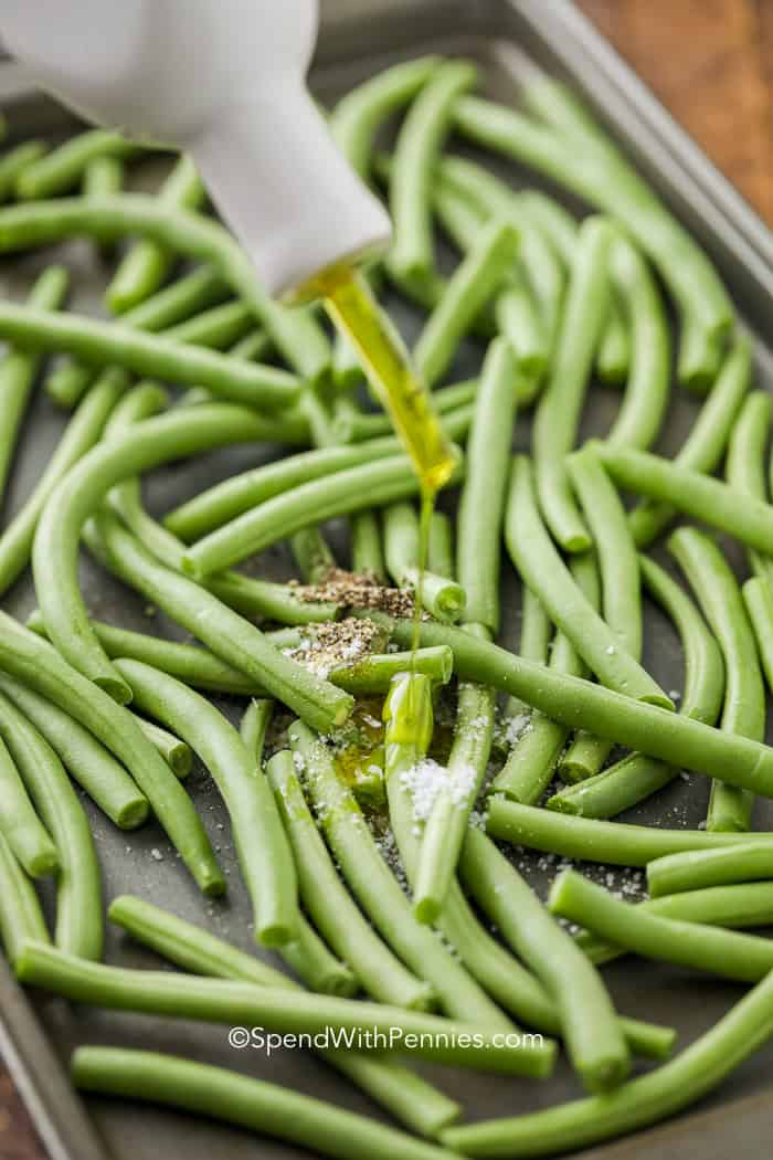 Adding olive oil to fresh green beans for making roasted green beans.