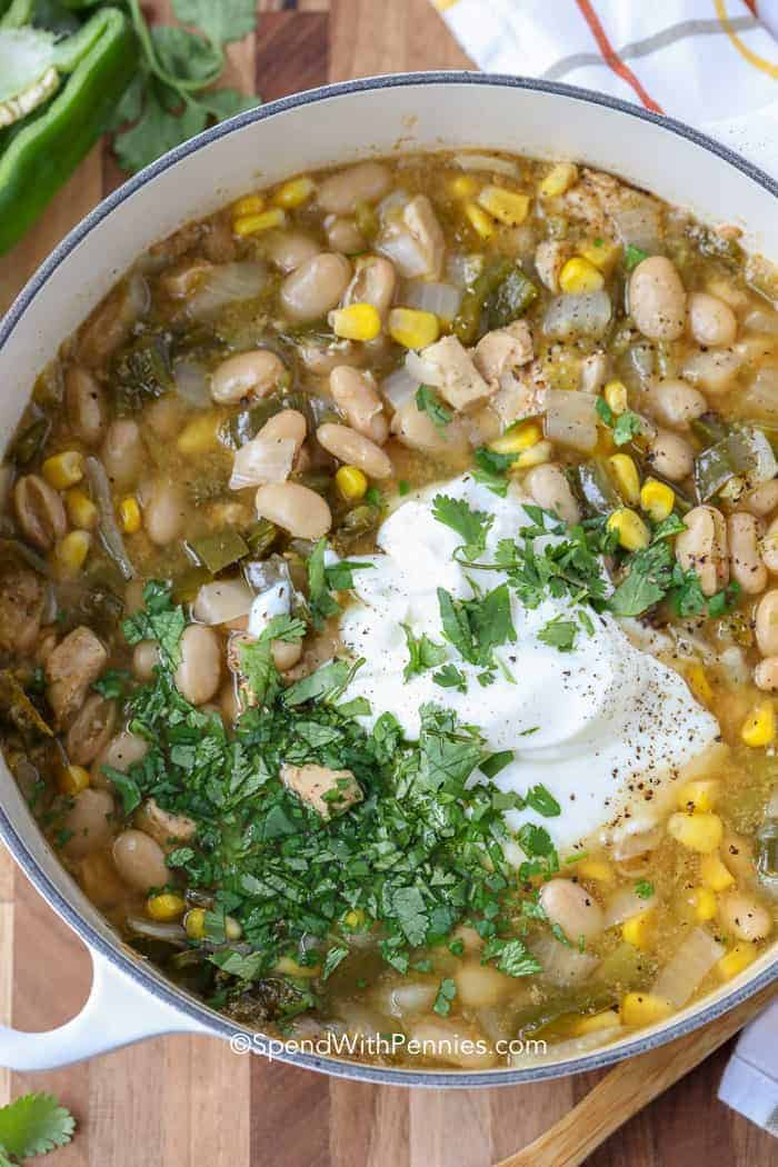 A pot of white chicken chili topped with sour cream and cilantro