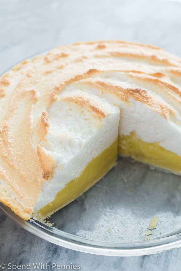 A pie plate of lemon meringue pie with a piece removed.
