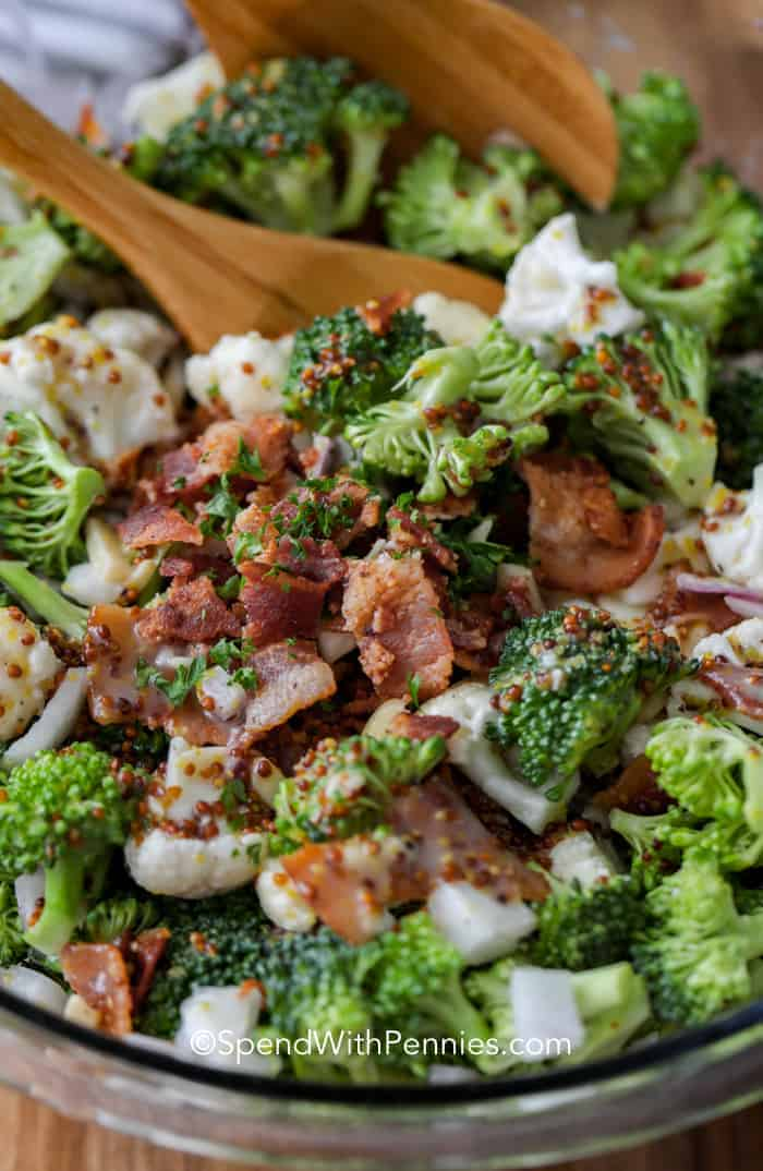 A close up of broccoli cauliflower salad full of bacon with serving spoons.