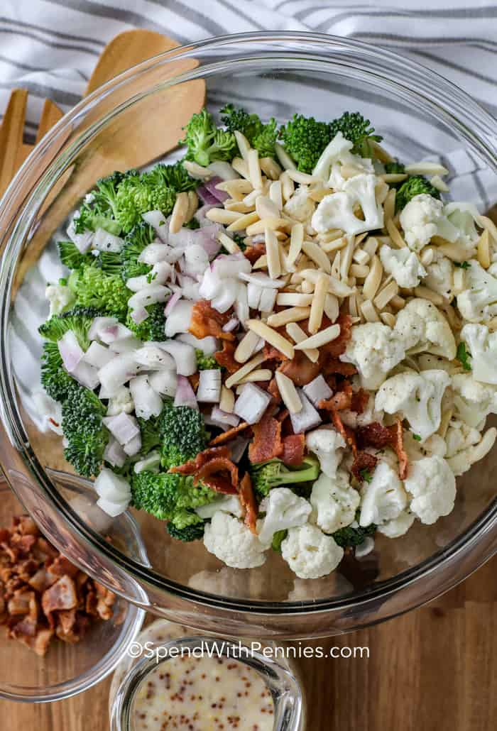 Broccoli cauliflower salad ingredients in a clear mixing bowl with dressing and bacon next to it.
